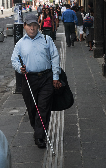 Blind man walking with cane