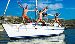 Affluent young people jumping off a yacht